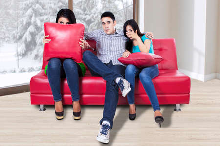 people watching: Three young teenagers are watching TV with fear at home