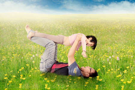 asian family outdoor: Portrait of cheerful young man and his daughter playing together on the meadow with blossom flowers at springtime Stock Photo