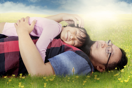 caress: Image of young father lying on green grass while caress his daughter at field with blossom flowers in springtime Stock Photo