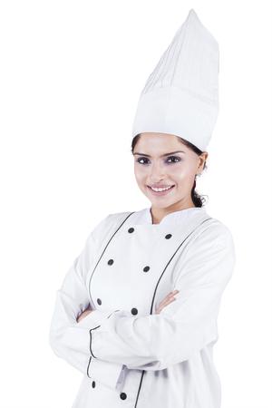 Portret van mooie Indische vrouw chef-kok in de studio tijdens het dragen van werkkleding en gekruiste handen Stockfoto