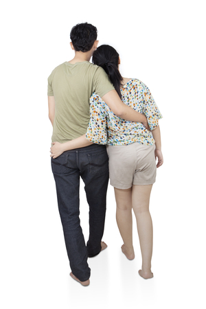 Back view of romantic young couple  hug and look into the distance, isolated on white background Stock Photo