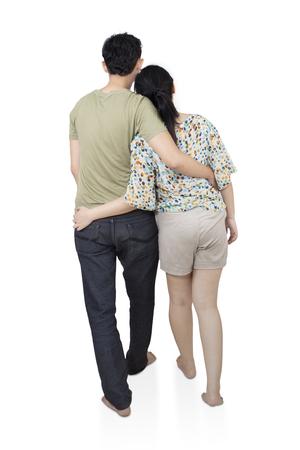 Vue arrière du jeune couple romantique étreinte et regarder au loin, isolé sur fond blanc