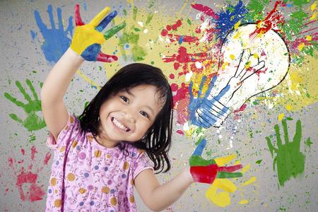 Portret van vrolijke en creatieve klein meisje met haar geschilderde handen met kleurrijke verf