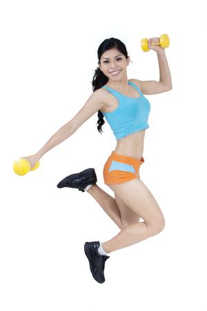 ropa deportiva: Mujer atractiva vistiendo ropa deportiva y salto en el estudio, mientras que la celebración de dos mancuernas Foto de archivo