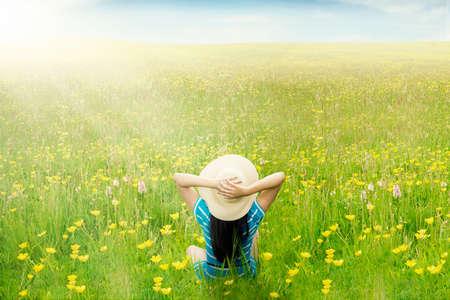 campo de flores: Vista posterior de la mujer feliz se relaja en el prado verde mientras se está sentado y disfrutar de flor de las flores en primavera