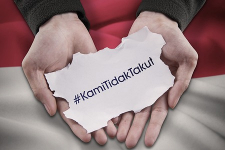 guerrilla: Image of two hands holding a paper with text of #KamiTidakTakut in front of Indonesian flag