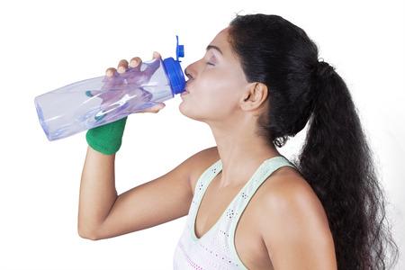 tomando agua: Mujer joven india agua potable de una botella después del entrenamiento en el estudio, aislado en blanco Foto de archivo