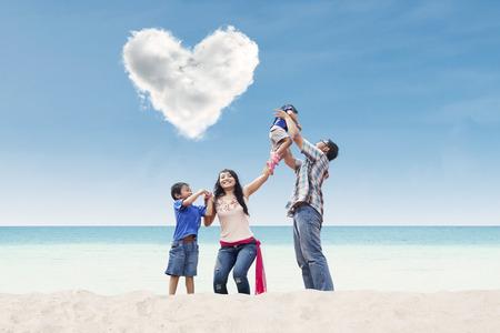 under heart: Asian family under heart shape cloud on the beach