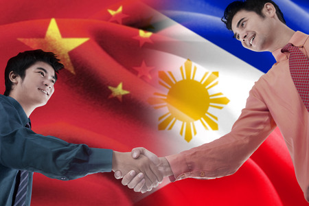 alliance: Photo of two young businessmen shaking hands with flag of China and Philippines