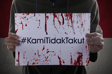 the indonesian flag: Image of hands holding bloody paper and shows message with #KamiTidakTakut in front of Indonesian flag