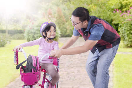 teach: Portrait of young father teaching his daughter to ride bicycle on the park at springtime
