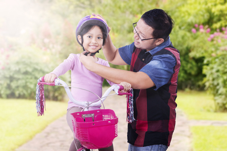 fastens: Picture of young man fastens helmet on his daughter before ride a bicycle at the park