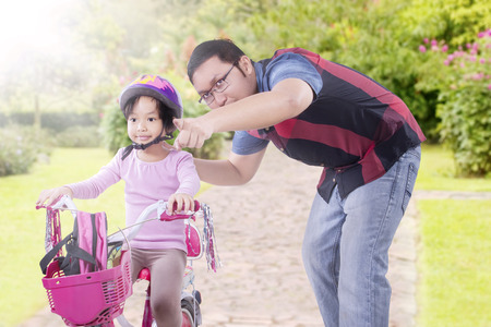 indian summer: Young father teach and guide his daughter to ride bicycle on the park at springtime Stock Photo