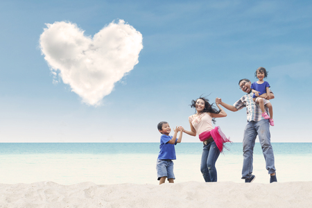 whitehaven: Happy family enjoy time at beach under love cloud Stock Photo