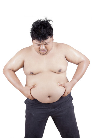 big belly: Portrait of young overweight person holding his big stomach in the studio, isolated on white background