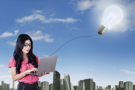 idea bulb: Picture of creative young businesswoman using laptop computer with light bulb attached to it Stock Photo