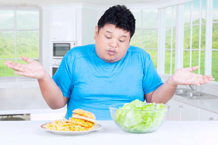 man portrait: Photo of a fat person looks confused to choose a bowl of salad or hamburger on the plate, shot in the kitchen Stock Photo