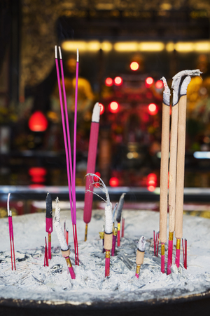 buddhism prayer belief: Close up burning incense with ash to pray in the temple Stock Photo