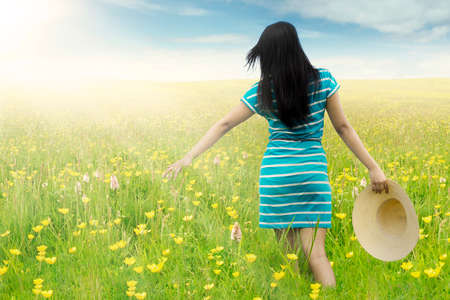 feels: Rear view of happy woman walking on the meadow while touching blossom flowers while carrying hat Stock Photo