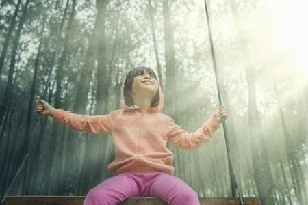 swings: Beautiful little girl sitting on a swing while wearing jacket in the pine forest Stock Photo