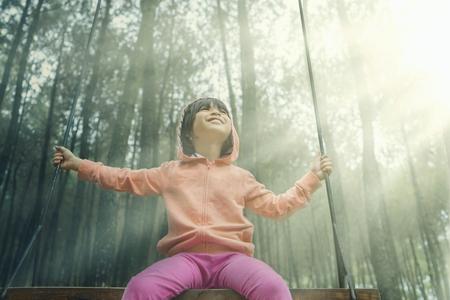 columpio: Hermosa niña sentada en un columpio, mientras que el uso de chaqueta en el pinar