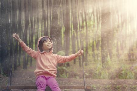niños felices: Retrato de la niña bonita sentado en un columpio en el bosque de pino con luz del sol en la mañana