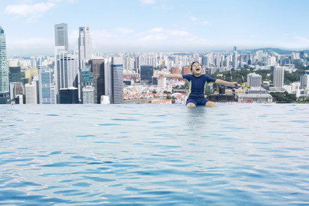 arena: Retrato de niño alegre disfrutar de las vacaciones y se divierten en una piscina en la azotea Foto de archivo
