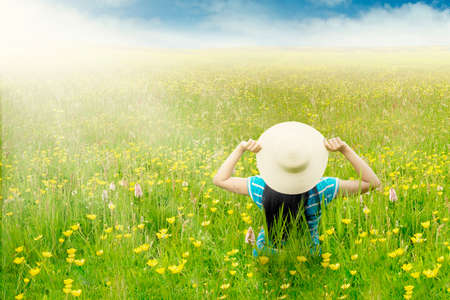 yellow blossom: Rear view of woman wearing hat and sitting on the blossom meadow with yellow flowers at springtime Stock Photo