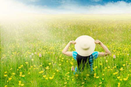 campo de flores: Vista trasera de una mujer que lleva el sombrero y sentado en el prado de la flor con flores amarillas en primavera
