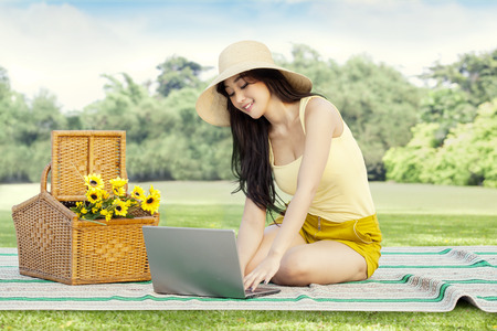 grass flower: Portrait of beautiful asian woman with casual clothes, sitting on mat while using laptop at field