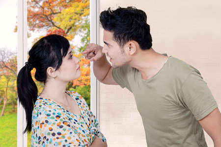 young wife: Picture of emotional young man scolding his wife while pointing her face at home