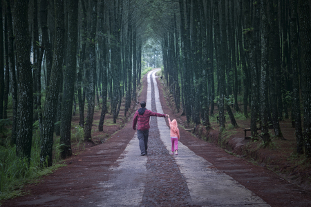 Young man walking in the pine forest while holding hands with his daughter