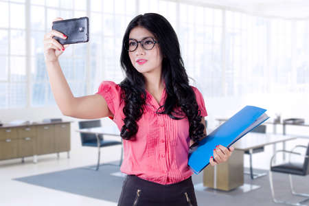 asian businesswoman: Pretty young asian businesswoman taking selfie picture in the office with a mobile phone