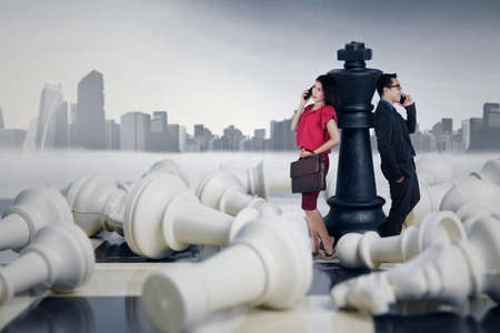 pawn adult: Two young successful entrepreneurs standing on the chessboard and lean on the chess queen while talking on the phone