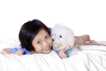 mignonne petite fille: Portrait d'une petite fille mignonne souriant à la caméra en position couchée sur la chambre à coucher avec un chien maltese, isolé sur fond blanc