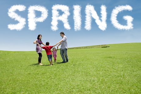 kids hand: Group of cheerful family enjoy recreation on the park and make a circle together under a spring cloud