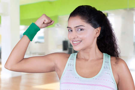 strong women: Beautiful indian woman smiling at the camera while wearing sportswear and showing her bicep after workout at gym