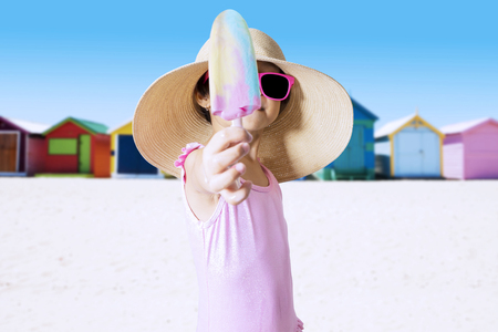 pink bikini: Little child holding ice cream and offering to the camera while wearing bikini on the beach
