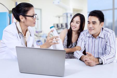 femme médecin d'Asie avec le jeune couple dans une clinique