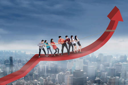 group of workers: Crowd of businesspeople pulling arrow upward by using a rope above the city Stock Photo