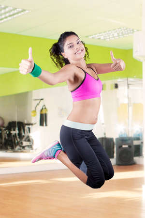 hand weight: Image of pretty indian woman wearing sportswear and jumping in the fitness center while showing thumbs up