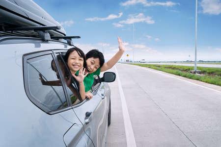 Portrait de deux enfants heureux agitant la main sur l'appareil photo tout en collant leur tête par la fenêtre de voiture