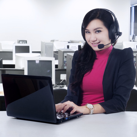 tech support: Portrait of beautiful helpline operator using laptop computer and headset to work in the office room