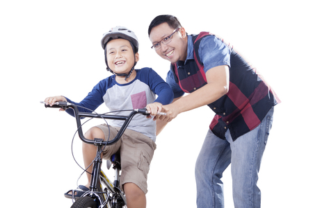 helps: Portrait of young dad helps his son to ride a bike while holding the bike, isolated on white background Stock Photo