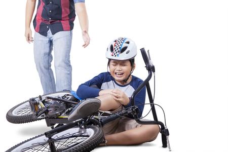 de rodillas: ni�o herido que cae de su bicicleta y llorando mientras mantiene su rodilla con el pap� viene a ayudar, aislado en blanco Foto de archivo