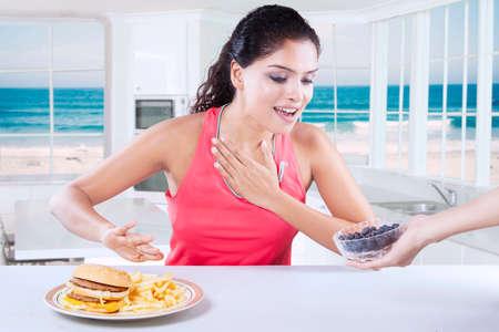comida chatarra: Imagen de la mujer sana de elegir entre un plato de fruta de arándano y la hamburguesa en la cocina con la playa de fondo en la ventana