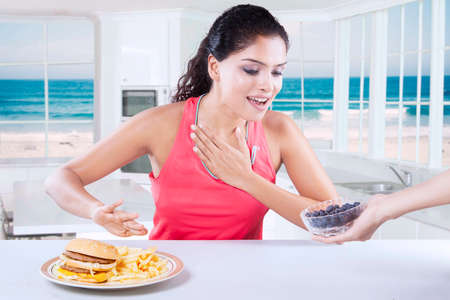 beach window: Picture of healthy woman choosing between a bowl of blueberry fruit and hamburger in the kitchen with beach background on the window