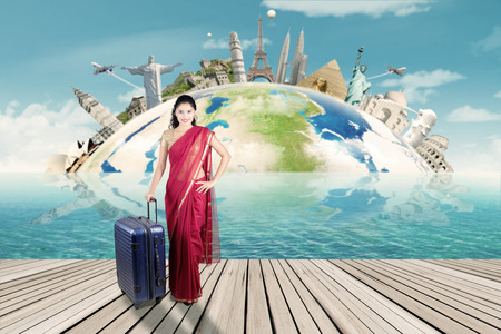 Beautiful indian woman carrying suitcase with map of world monument. Concept of travel around the world
