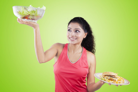 eating food: Beautiful young model lifting healthy food and fast food with green background