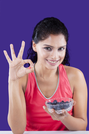 woman eating fruit: Image of attractive female model showing OK sign while holding fresh blueberry fruit on the bowl